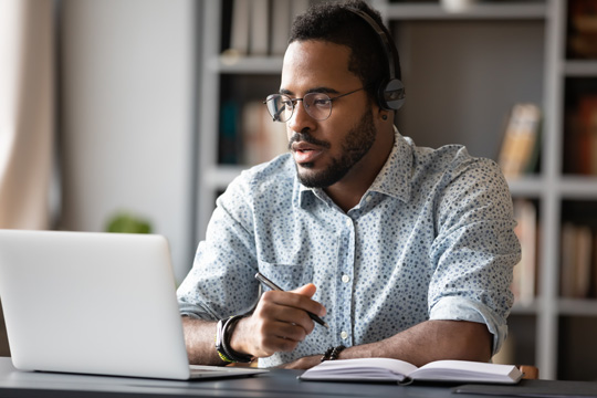 Man at his desk looking at his computer