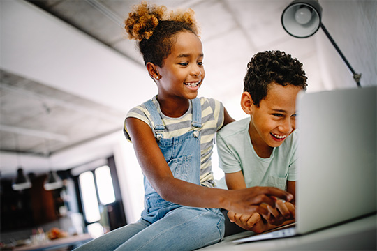 Two young kids playing on the computer
